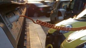 Pequeño coche eléctrico en la estación de carga en la calle de la ciudad Transporte de Eco y fuente de alimentación metrajes