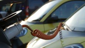 Pequeño coche eléctrico en la estación de carga en la calle de la ciudad Transporte de Eco y fuente de alimentación almacen de video