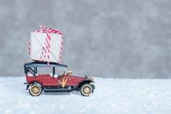 Pequeño coche retro con el regalo en el tejado Fotografía de archivo