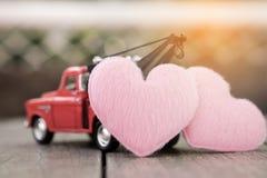 Pequeño coche rojo del juguete y corazones rosados para el día del ` s de la tarjeta del día de San Valentín Imagen de archivo libre de regalías