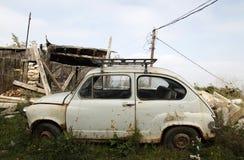 Pequeño coche viejo delante de una casa vieja Fotos de archivo