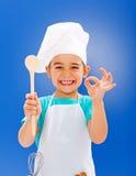 Pequeño cocinero alegre que muestra buen gusto Fotografía de archivo