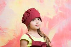 Pequeño cocinero de la muchacha con la cara adorable en sombrero y delantal Foto de archivo libre de regalías