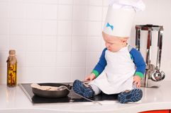 Pequeño cocinero del bebé en el sombrero del cocinero que hace las crepes Fotografía de archivo
