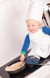 Pequeño cocinero del bebé en el sombrero del cocinero que hace las crepes Foto de archivo libre de regalías