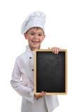 Pequeño cocinero divertido en el uniforme del blanco que sostiene una pizarra, en el fondo blanco foto de archivo libre de regalías