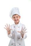 Pequeño cocinero juguetón lindo con la harina en sus manos Imagen de archivo libre de regalías