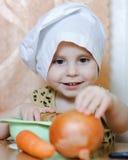 Pequeño cocinero lindo hermoso con las verduras Imagen de archivo libre de regalías