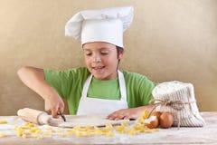 Pequeño cocinero que corta las pastas de la fabricación de pastas Foto de archivo libre de regalías