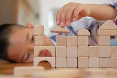pequeño colegial asiático de los niños del niño del muchacho del niño que juega el bloque de madera imágenes de archivo libres de regalías