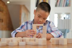 pequeño colegial asiático de los niños del niño del muchacho del niño que juega el bloque de madera fotografía de archivo libre de regalías