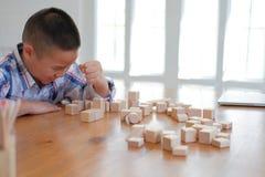 pequeño colegial asiático de los niños del niño del muchacho del niño que juega el bloque de madera fotos de archivo libres de regalías