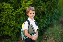 Pequeño colegial del retrato con la mochila y los libros outdoors imagenes de archivo