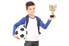 Pequeño colegial que sostiene fútbol y un trofeo Imagen de archivo libre de regalías