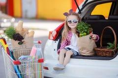 Pequeño comprador de la muchacha- de productos, sentándose en el tronco abierto de un coche Foto de archivo