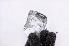 Pequeño control del cubo de hielo en la mano con los guantes Foto de archivo