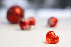 Pequeño corazón de cristal rojo con las chucherías rojas de la Navidad Imágenes de archivo libres de regalías