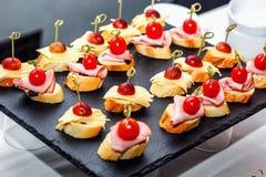 Pequeño crostini con el baguette asado a la parrilla, los tomates de cereza, las rebanadas del jamón, el queso y las uvas frescas Imágenes de archivo libres de regalías