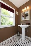 Pequeño cuarto de baño de Brown con el fregadero y los azulejos antiguos. Imagen de archivo