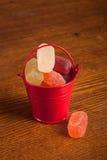 Pequeño cubo con el caramelo en el fondo de madera Foto de archivo libre de regalías