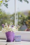 Pequeño cubo púrpura con las margaritas y la caja de regalo azul cerca del viento Fotos de archivo