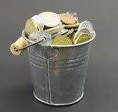 Pequeño cubo viejo natural del metal con las monedas Fotos de archivo
