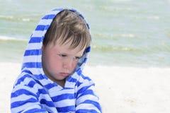 Pequeño daño lindo del niño y puesto mala cara, decepcionado Niño hermoso con dermatitis atópico en el fondo del mar, foto de archivo