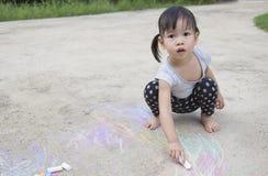 Pequeño dibujo asiático de la muchacha con tiza en la acera Imágenes de archivo libres de regalías