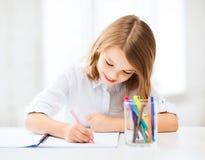 Pequeño dibujo de la muchacha del estudiante en la escuela Fotos de archivo libres de regalías
