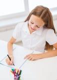 Pequeño dibujo de la muchacha del estudiante en la escuela Foto de archivo