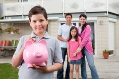 Pequeño dinero del ahorro del muchacho con la familia en la parte posterior Fotografía de archivo libre de regalías