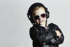 Pequeño disc jockey muchacho sonriente divertido en gafas de sol y auriculares Foto de archivo