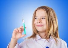 Pequeño doctor con la jeringuilla Foto de archivo libre de regalías