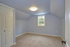 Pequeño dormitorio azul vacío acentuado con el techo saltado imagen de archivo