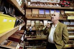 Pequeño dueño de tienda del tabaco que mira las cajas de cigarros en la exhibición en tienda imagen de archivo