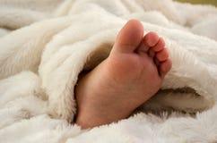 Pequeño, el pie de los niños en una manta blanca foto de archivo libre de regalías