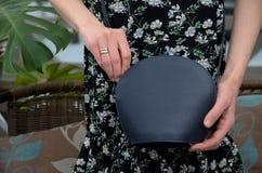 Pequeño embrague azul elegante del bolso de cuero en las manos de un fashi Fotografía de archivo libre de regalías