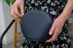 Pequeño embrague azul elegante del bolso de cuero en las manos de un fashi Fotos de archivo libres de regalías