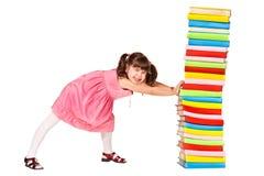Pequeño empuje de la colegiala a la pila de libros pesados Fotografía de archivo libre de regalías