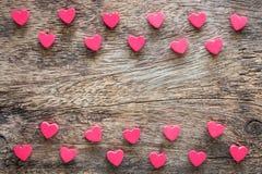 Pequeño en forma de corazón rojo en la textura de madera imagenes de archivo
