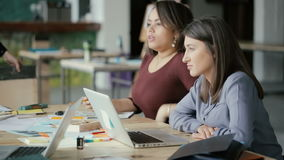 Pequeño equipo creativo del negocio que trabaja en oficina coworking La charla de dos mujeres, discutiendo idea y utiliza el orde almacen de video