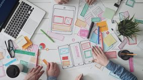 Pequeño equipo de diseñadores jovenes de UX que crean la disposición móvil del app almacen de metraje de vídeo