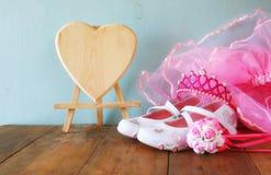 Pequeño equipo del partido de las muchachas: flores blancas de los zapatos, de la corona y de la vara en la tabla de madera traje Imagen de archivo