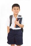 Pequeño escolar asiático que sostiene los libros con la mochila Fotos de archivo