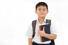 Pequeño escolar asiático que sostiene los libros con la mochila Fotos de archivo libres de regalías