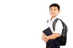 Pequeño escolar asiático que sostiene los libros con la mochila Fotografía de archivo