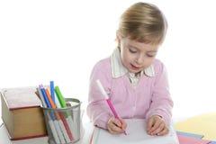 Pequeño escritorio de escritura rubio de la muchacha del estudiante Foto de archivo libre de regalías
