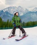 Pequeño esquiador en centro turístico del cielo de la montaña Fotografía de archivo libre de regalías