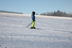 Pequeño esquiador en el piste con un casco en su cabeza Conveniente para el uso promocional, en vez del título Fotos de archivo libres de regalías