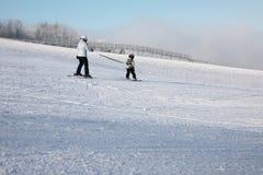 Pequeño esquiador en las cuestas acompañadas con un casco en su cabeza Atan al esquiador a una cuerda de la seguridad Imagenes de archivo